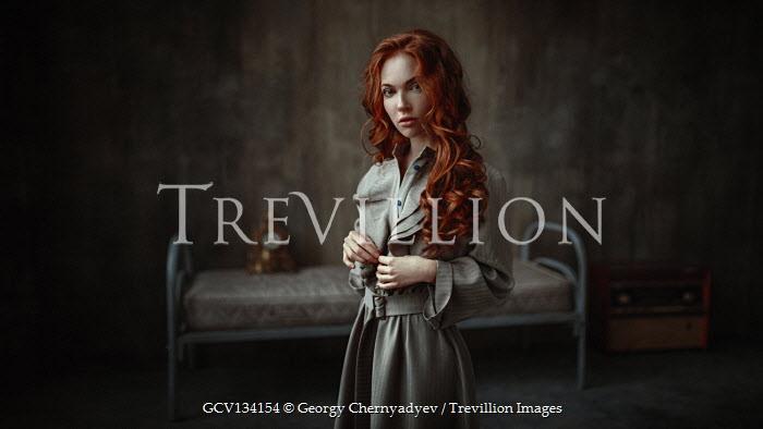 Georgy Chernyadyev WOMAN WITH RED HAIR STANDING IN BLEAK BEDROOM