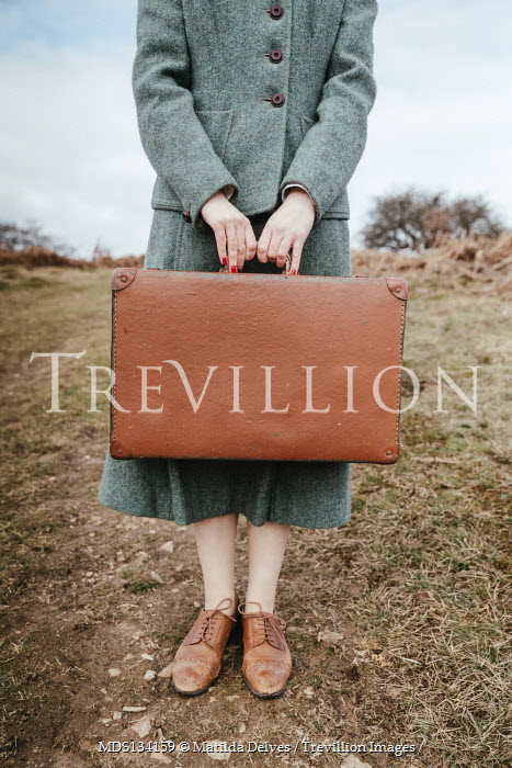 Matilda Delves WOMAN HOLDING SUITCASE IN COUNTRYSIDE