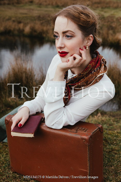 Matilda Delves RETRO WOMAN WITH SUITCASE AND BOOK BY POND