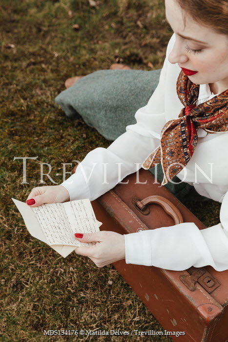Matilda Delves RETRO WOMAN SITTING WITH SUITCASE READING LETTER