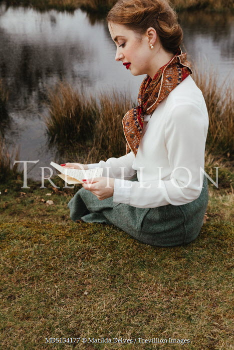 Matilda Delves RETRO WOMAN SITTING BY RIVER READING LETTER