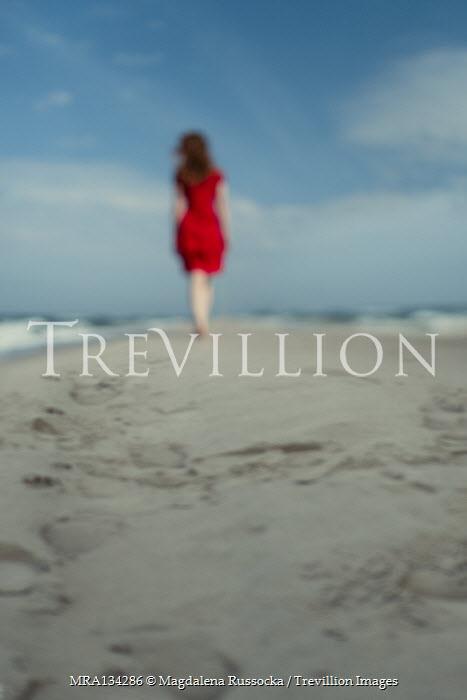 Magdalena Russocka woman in red dress walking on beach