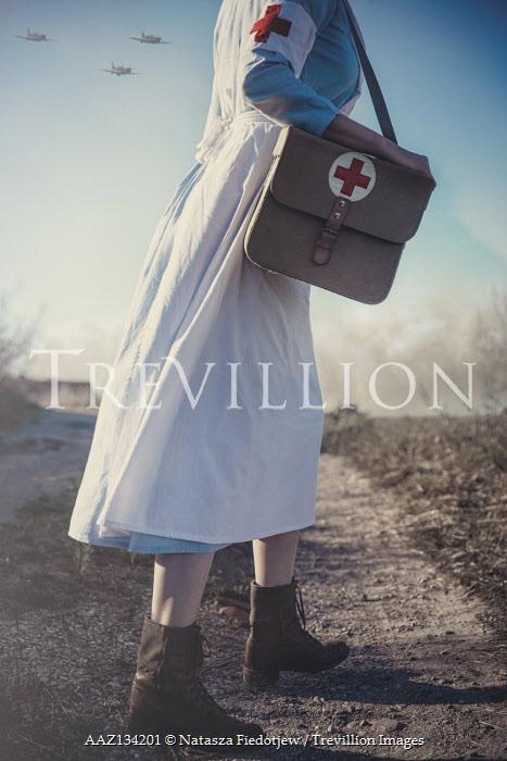 Natasza Fiedotjew war nurse on country road holding medic bag watching aeroplanes