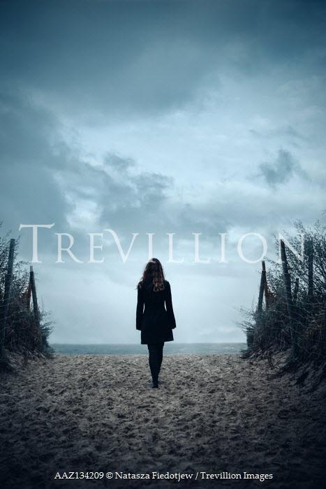 Natasza Fiedotjew woman in black jacket entering seashore