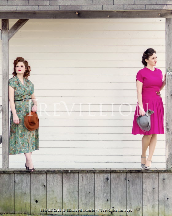 Elisabeth Ansley TWO RETRO WOMEN HOLDING HATS ON VERANDA