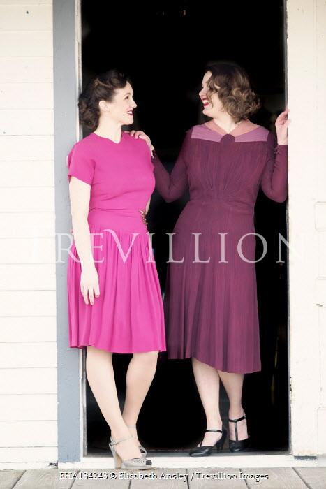 Elisabeth Ansley TWO RETRO WOMEN STANDING IN OPEN DOORWAY