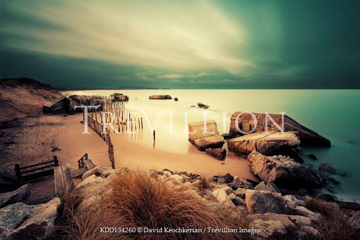 David Keochkerian MAN ON BEACH STANDING BY WARTIME BUNKER