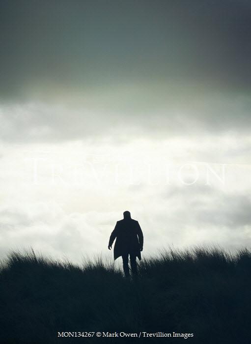 Mark Owen SILHOUETTED MAN IN COAT WALKING IN FIELD