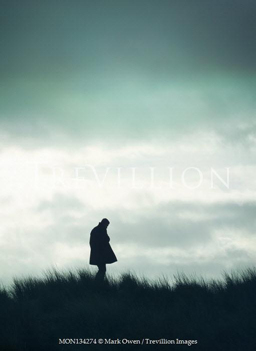 Mark Owen SILHOUETTED MAN IN COAT STANDING IN FIELD