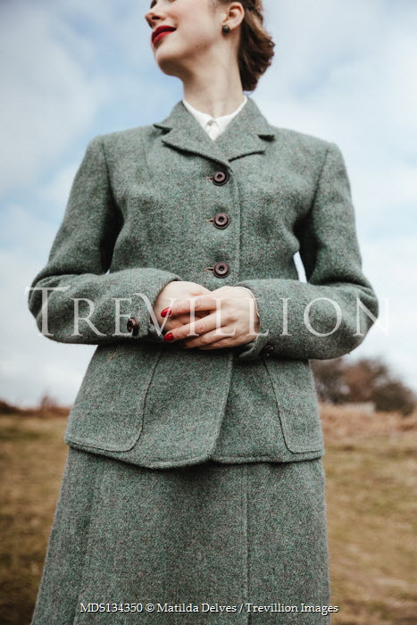Matilda Delves RETRO WOMAN IN SUIT STANDING IN COUNTRYSIDE