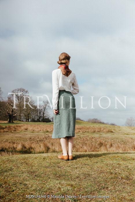 Matilda Delves RETRO WOMAN STANDING BY RURAL RIVER