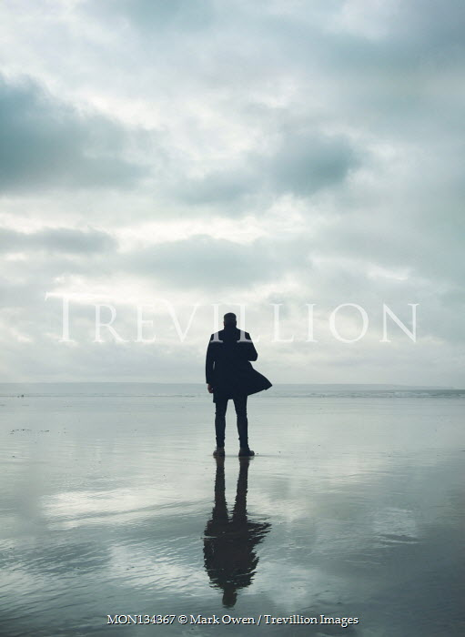 Mark Owen SILHOUETTED MAN IN COAT STANDING ON BEACH