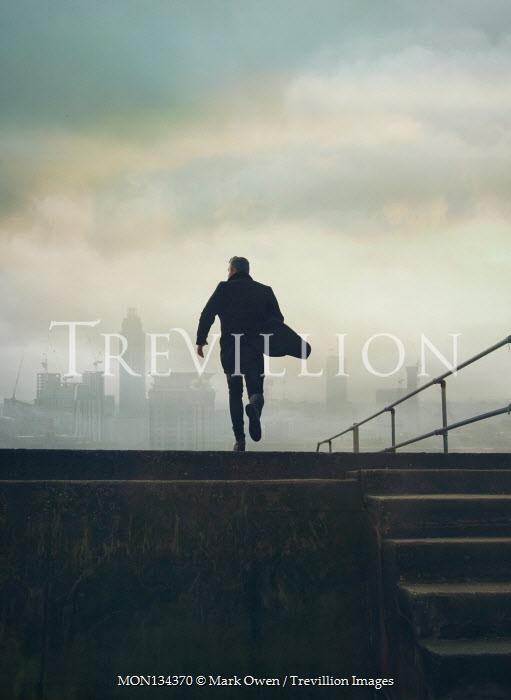 Mark Owen MAN IN COAT RUNNING BY STEPS IN CITY