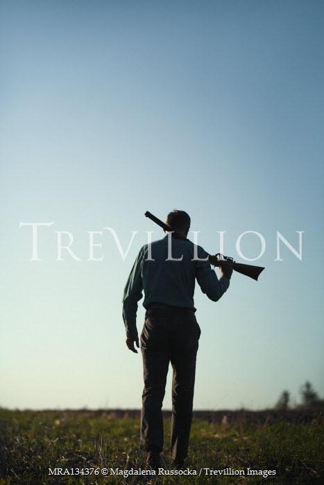 Magdalena Russocka man holding rifle walking in field