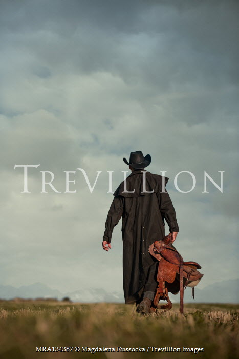 Magdalena Russocka cowboy man carrying saddle walking in field