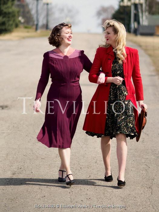 Elisabeth Ansley HAPPY WOMEN WALKING ARM IN ARM IN ROAD