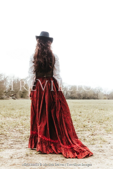 Matilda Delves HISTORICAL WOMAN WITH STETSON STANDING IN COUNTRYSIDE