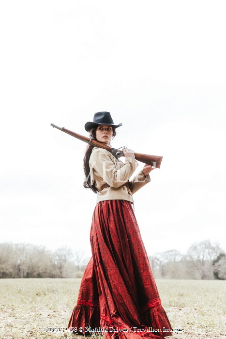 Matilda Delves HISTORICAL WOMAN WITH STETSON AND RIFLE OUTDOORS