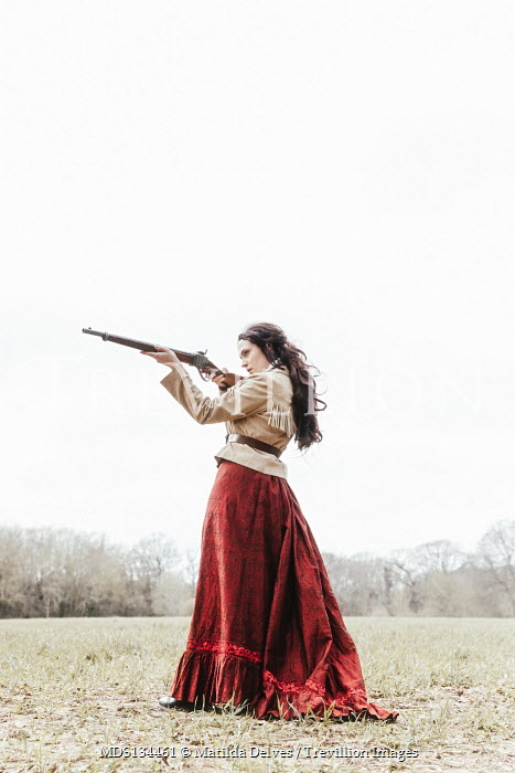 Matilda Delves HISTORICAL WOMAN POINTING RIFLE IN COUNTRYSIDE