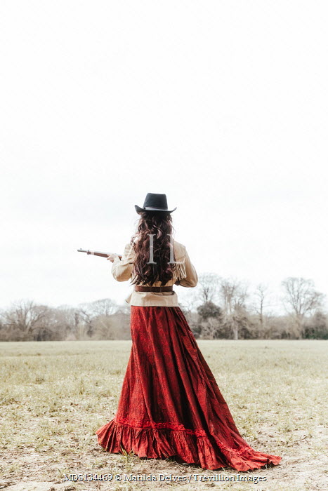 Matilda Delves HISTORICAL WOMAN WITH HAT AND RIFLE IN COUNTRYSIDE