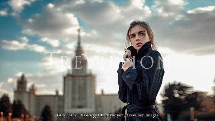 Georgy Chernyadyev WOMAN IN RAINCOAT STANDING BY GRAND BUILDING