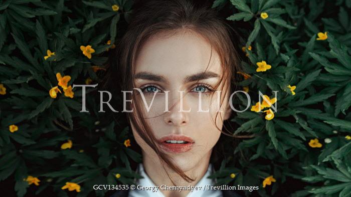 Georgy Chernyadyev BRUNETTE WOMAN LYING WITH YELLOW FLOWERS OUTDOORS