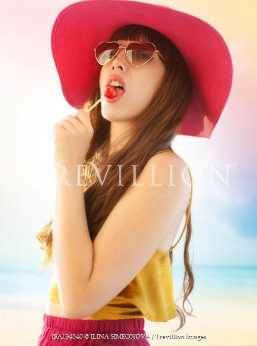 ILINA SIMEONOVA WOMAN IN HAT LICKING LOLLIPOP ON BEACH