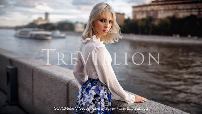 Georgy Chernyadyev SERIOUS BLONDE WOMAN STANDING BY URBAN RIVER