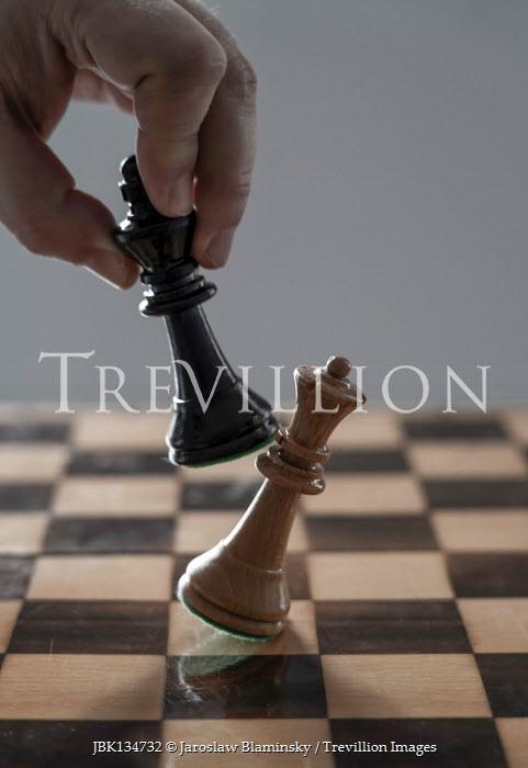 Jaroslaw Blaminsky Man's hand with chess pieces on board