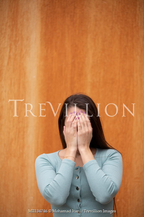 Mohamad Itani Young woman covering her face