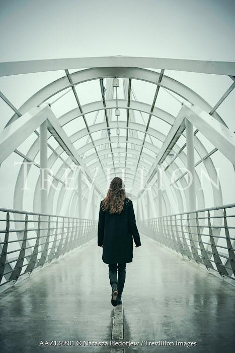 Natasza Fiedotjew woman in black walking on bridge