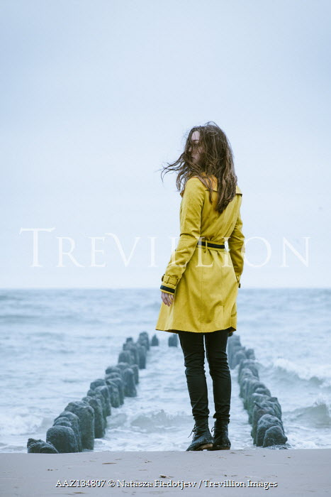 Natasza Fiedotjew woman in yellow coat standing on beach