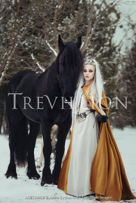 Anna Sychowicz Young woman in yellow cloak with horse in snow