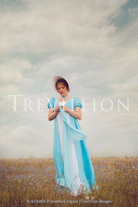 Joanna Czogala Young woman with Regency blue dress and bonnet in field