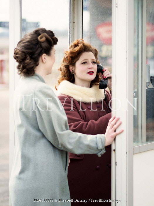 Elisabeth Ansley TWO RETRO WOMAN STANDING IN TELEPHONE BOX