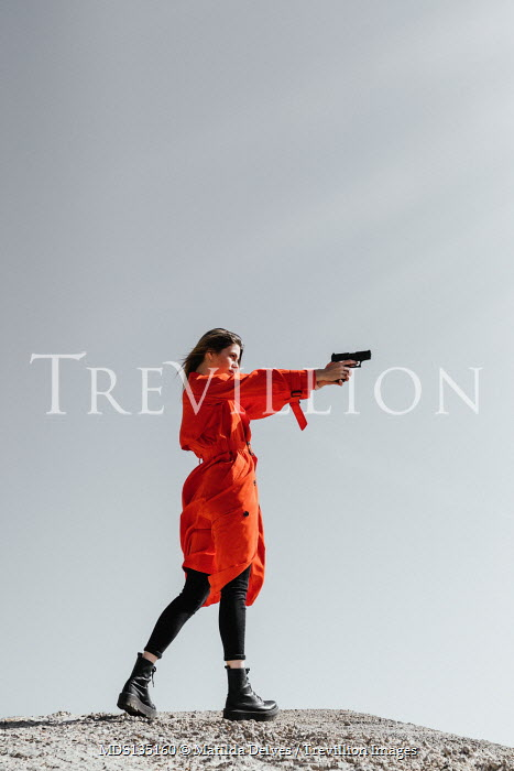Matilda Delves WOMAN IN RED COAT POINTING GUN OUTDOORS