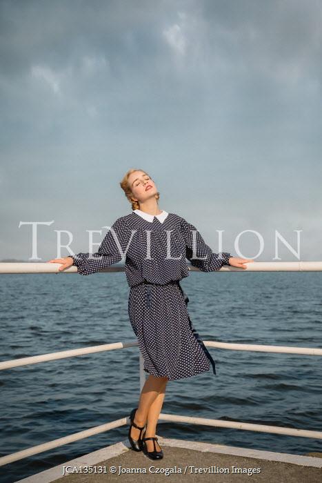 Joanna Czogala BLONDE RETRO WOMAN BY RAILINGS AND SEA