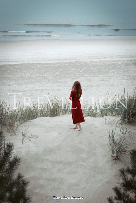 Natasza Fiedotjew woman in red dress standing on dune by sea