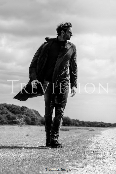 CollaborationJS MAN IN COAT WALKING IN WINDY COUNTRYSIDE