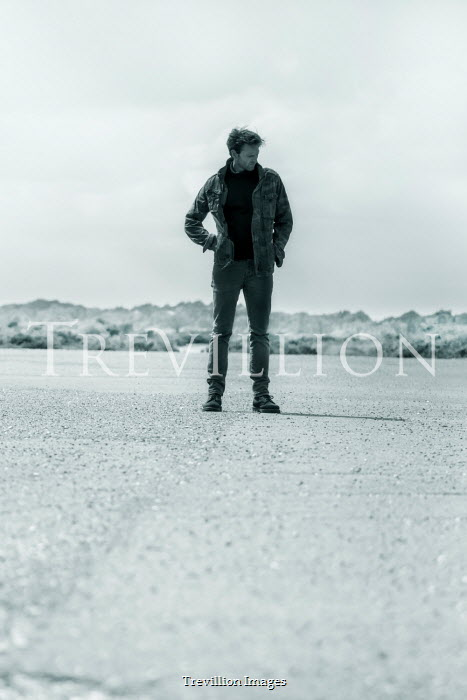 CollaborationJS MAN IN DENIM JACKET STANDING IN COUNTRYSIDE
