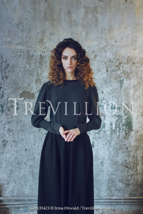 Irina Orwald SERIOUS GIRL WITH CURLY HAIR STANDING BY WALL