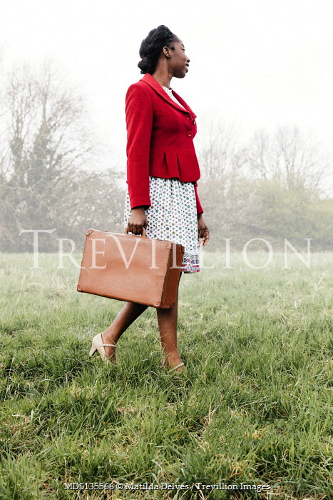 Matilda Delves WOMAN IN RED JACKET WITH SUITCASE WALKING IN FIELD