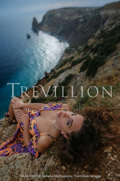 Tatiana Mertsalova WOMAN IN FLORAL DRESS LYING ON CLIFF BY SEA