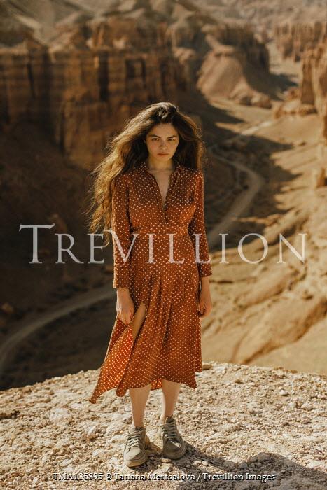 Tatiana Mertsalova WOMAN WITH LONG DARK HAIR LYING ON CLIFF IN CANYON