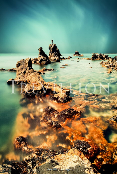 David Keochkerian DISTANT MAN STANDING ON ROCK IN SEA