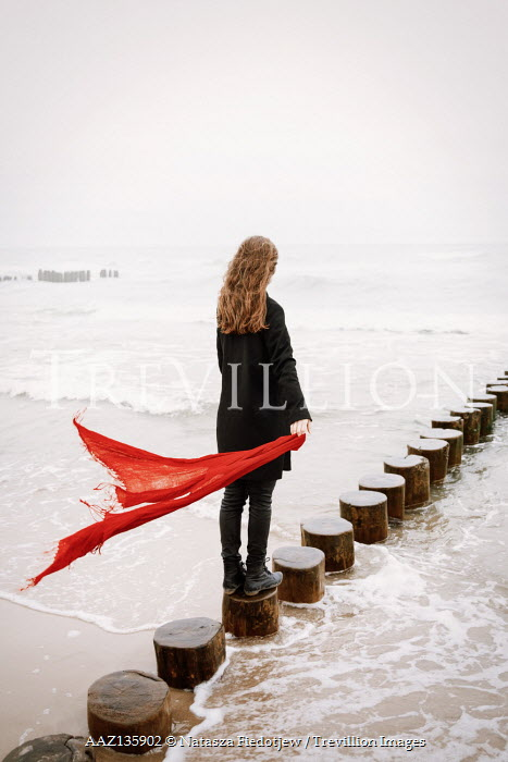 Natasza Fiedotjew woman at seaside holding red scarf in wind
