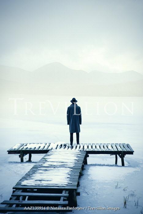 Natasza Fiedotjew man in black coat and fedora hat standing on jetty in winter