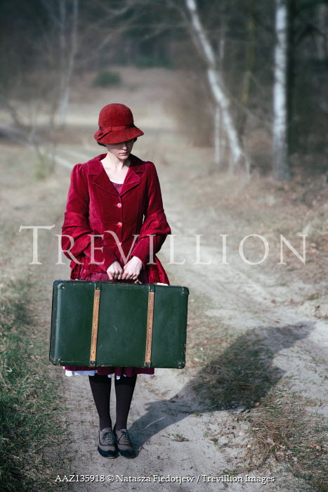 Natasza Fiedotjew vintage woman in red holding suitcase standing on country road