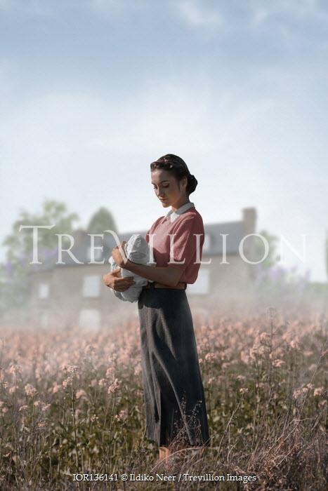 Ildiko Neer Vintage woman holding baby in meadow by house