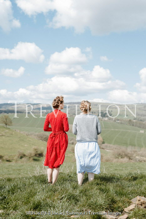 Shelley Richmond TWO RETRO WOMEN STANDING IN COUNTRYSIDE